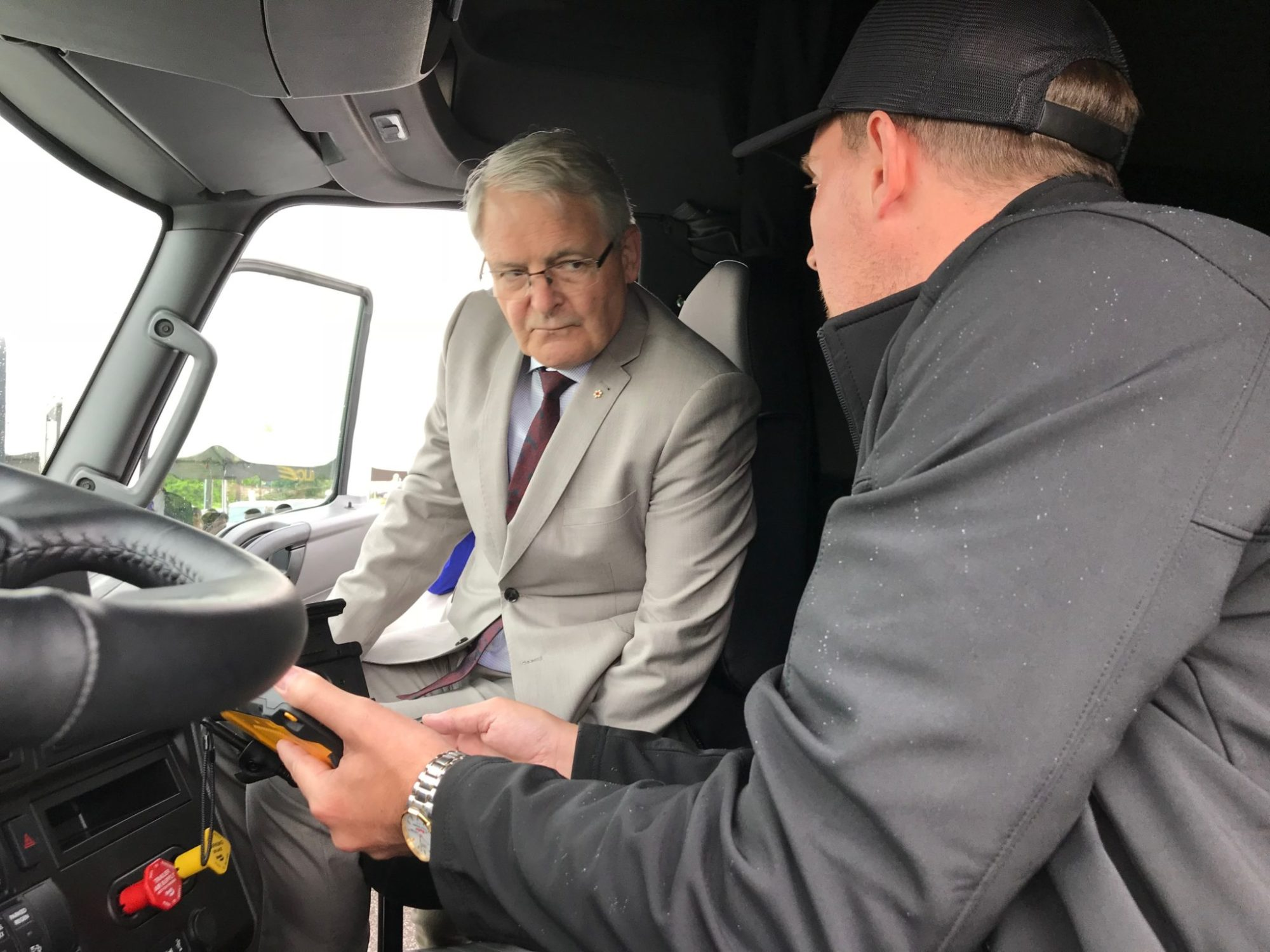 Federal Transport Minister Marc Garneau views an ELD that will track truck driver hours of service